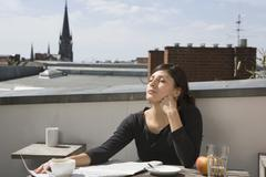 Stock Photo of Woman sitting on a rooftop in the sun