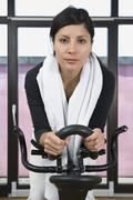 A woman on an exercise bike Stock Photos