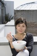 Stock Photo of A woman eating breakfast on a roof terrace