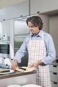 A mature man preparing sushi in the kitchen Stock Photos