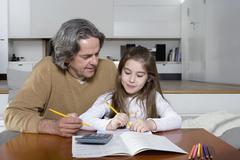 A father helping his daughter with her homework Stock Photos