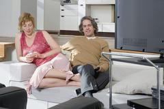 Nainen käyttää matkapuhelinta vieressä mies katselee televisiota Kuvituskuvat