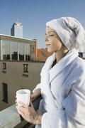 Stock Photo of A woman standing on a rooftop terrace wearing a bathrobe and towel