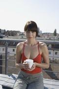 Stock Photo of A woman sitting on a rooftop terrace with a cup of tea