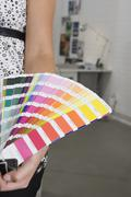 A woman holding a color swatch Stock Photos