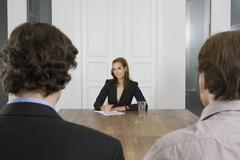 A woman meeting with two men in a board room Stock Photos
