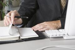 Detail of a businessman using a personal organizer at his desk Stock Photos