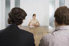 A woman meeting with two men in a board room - stock photo
