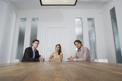 Three people sitting at a table in a conference room Stock Photos
