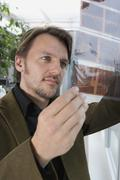 A man looking at a slide contact sheet Stock Photos