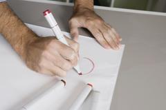 A man drawing on a sheet of paper with a felt tip pen Stock Photos