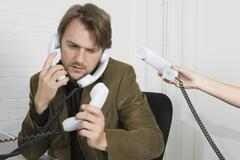 A businessman with four telephone receivers Stock Photos