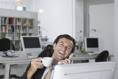 A businessman on the phone in an office Stock Photos