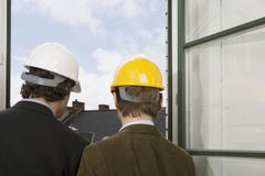 Rear view of two men standing by a window wearing hardhats - stock photo
