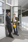 Two men standing by a window holding hardhats and architecural plans - stock photo