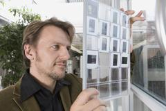 Stock Photo of A man looking at a contact sheet of slides