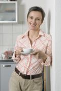A Mature Woman leaning against a wall holding a coffee cup and saucer - stock photo