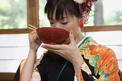 A woman wearing a kimono and eating soup Stock Photos
