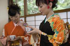 Two women wearing kimonos drinking tea - stock photo