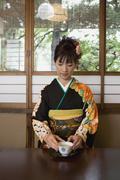 A woman wearing kimono and drinking tea - stock photo