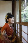 A woman wearing a kimono looking through a window - stock photo