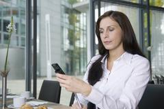 A woman using her mobile phone in a resturant Stock Photos