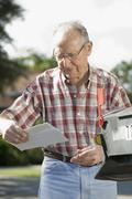 A senior man checking the mailbox - stock photo