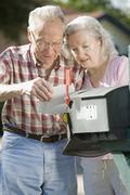 A senior couple checking the mailbox - stock photo