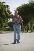 A senior man walking in the street and waving Stock Photos
