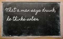 expression -  what a man says drunk, he thinks sober - written on a school bl - stock illustration