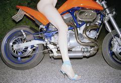 A semi-dressed woman sitting on a motorbike Stock Photos