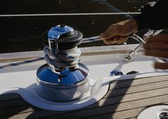 A person winding rope around a crank on a yacht Stock Photos
