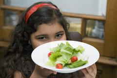 A girl holding a bowl of salad Stock Photos