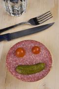 An anthropomorphic face on a slice of salami - stock photo
