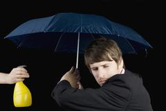 A man being squirted from a water bottle and holding an umbrella Stock Photos