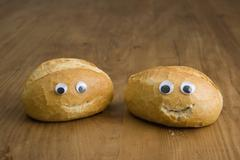 Two bread buns with anthropomorphic faces - stock photo
