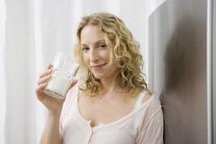 A woman drinking a glass of milk Stock Photos