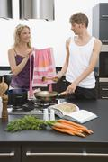 A woman showing a pink apron to a man - stock photo