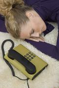 A woman asleep next to a landline phone Stock Photos