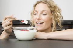 A woman holding a spoon of yogurt and raspberries up to her mouth Stock Photos