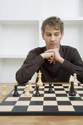 A mid adult man contemplating a chessboard - stock photo