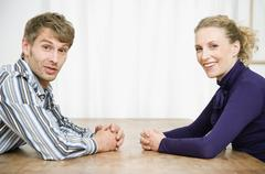 A mid adult couple sitting face to face and smiling Stock Photos