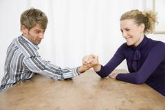 A mid adult couple arm wrestling Stock Photos
