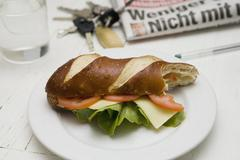 A submarine sandwich with tomato, lettuce and cheese on a plate with a bite out - stock photo