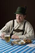 stereotypical German man in Bavarian costume with a beer and German meal - stock photo