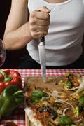 Stereotypical Italian Man sticking a knife in a cutting board aggressively, - stock photo