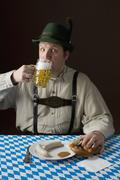 Stock Photo of Stereotypical German man in Bavarian costume drinking a beer and German meal