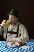 Stereotypical German man in Bavarian costume drinking a beer and German meal - stock photo