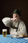 Stereotypical German man in Bavarian costume wiping mouth at a table with a beer - stock photo