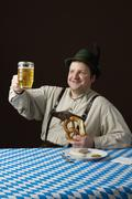 Stereotypical German Man toasting a glass of beer and holding a pretzel - stock photo